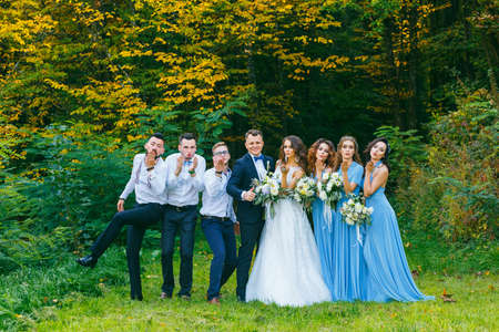 Groomsmen and bridesmaids sends an air kiss to the camera in nature in summer Stock Photo