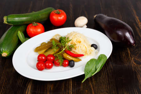 Pickled vegetables. Appetizer of tomatoes, cucumbers, cabbage and pepper close-up in white plate on the wooden table Stock Photo