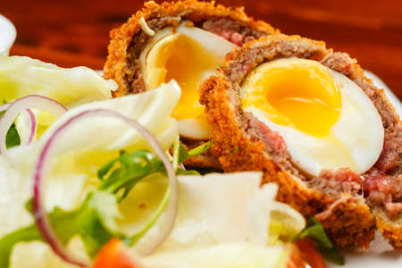 scottish culture: English food, Scotch eggs served with lettuce, toatoes and sauce