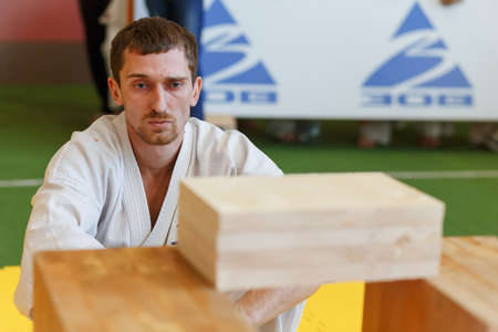 GRODNO, BELARUS - APRIL 22, 2017: Sportsmen preparing for the competition by breaking wooden boards with his hands in the championship among juniors of the Grodno region Kyokushin karate