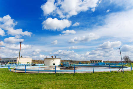 Water overflowing from round settlers on industrial sewage treatment plant Stock Photo