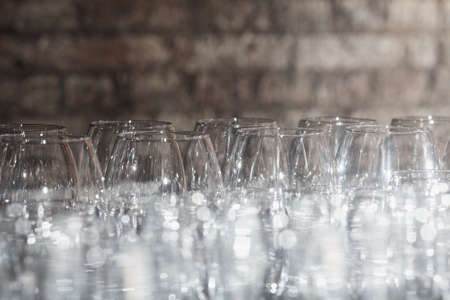 Lots of wine glasses on a brick wall background Stock Photo