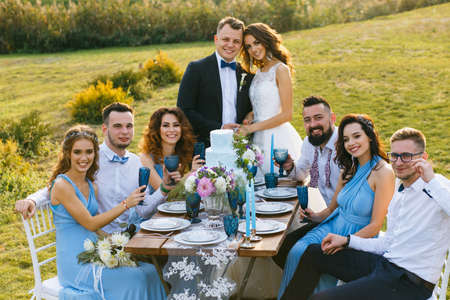 The newmarried couple and guests enjoy themselves at the Banquet table Stock Photo