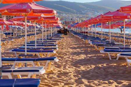 sep: NESSEBAR, BULGARIA - SEP 02, 2016: Beach umbrellas and sun loungers on a beach at sunrise in Nessebar, Bulgaria at September 02, 2016