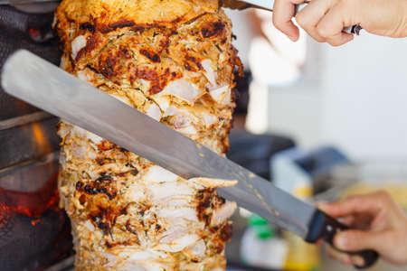 Shoarma vlees wordt gesneden voordat een broodje wordt gemaakt