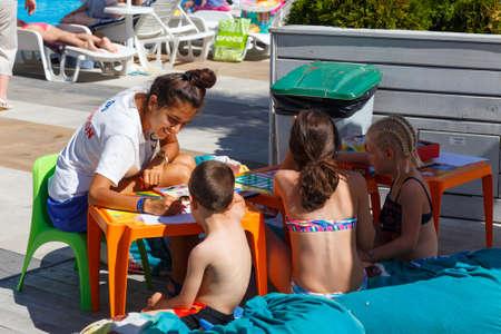 Nessebar, Bulgaria - September 01, 2016: The girl-the animator entertains children near the pool at the hotel