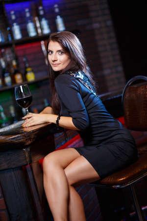 pretty woman in nightclub sitting alone have a glass of wine