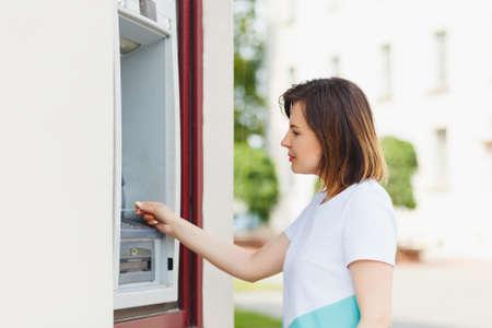 automatic transaction machine: Joven y bella mujer utilizando un cajero automático para obtener dinero en efectivo