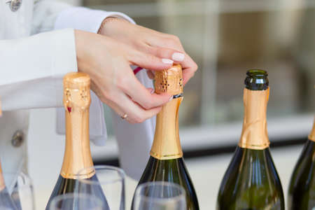 Hands of the steward opening bottles of champagne at the wedding ceremony