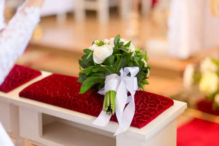tenderly: Wedding bouquet laying on bench in church during the wedding ceremony