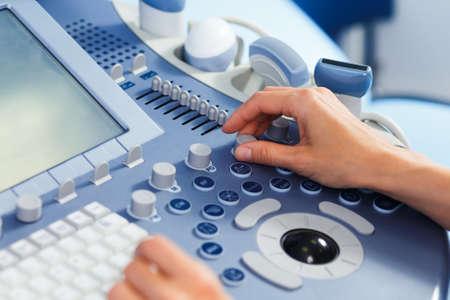 Handen van een arts die de medische echografie diagnostische machine gebruikt