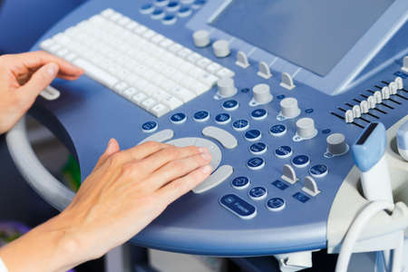 Hands of a doctor who uses the medical ultrasound diagnostic machine Stock Photo