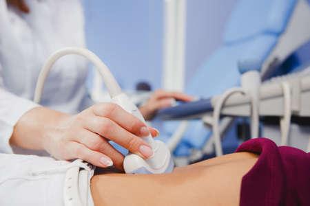 그녀의 여성 환자의 배를 검사하는 여성 의사 운영 초음파 스캐너