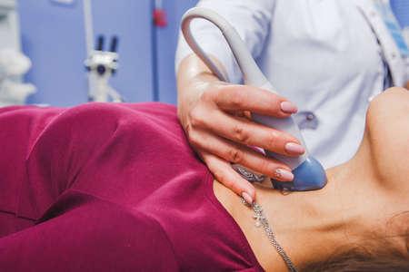 病院で超音波検査を行う若い女性