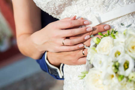 The couple cuddling and holding bridal bouquet. Hands close-up.