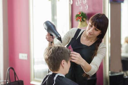 Grodno, ベラルーシ - 12月 13, 2017: 美容院で大人の女性の髪を乾燥美容師