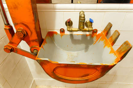 Washbasin stylized as the excavator boom in the toilet industrial style Archivio Fotografico