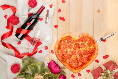 Heart shaped italian pizza with pepperoni and mozzarella and red wine bottle decorated with hearts and flowers. Valentines day greeting card. Top view Stock Photo