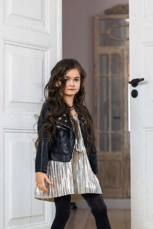Stylishly dressed girl in a leather jacket posing in a home interior