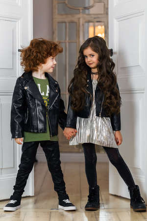 Stylishly dressed boy and girl in leather jackets posing together in a home interior