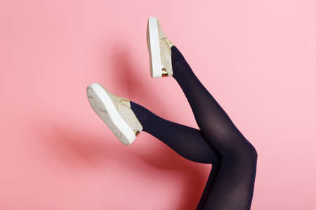 Legs of young caucasian woman in black tights and golden shoes on pink background