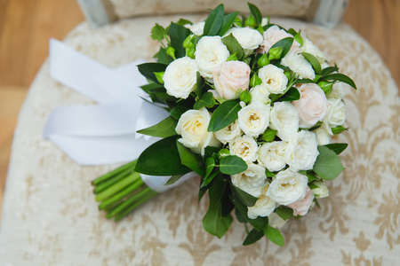 Wedding bouquet of white roses lying on a stone