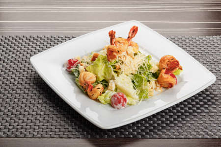 Traditional caesar salad with shrimp served on white square plate