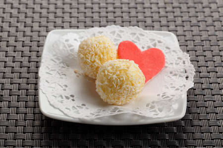 White chocolate candy coconut truffles on plate swcorated with heart cake