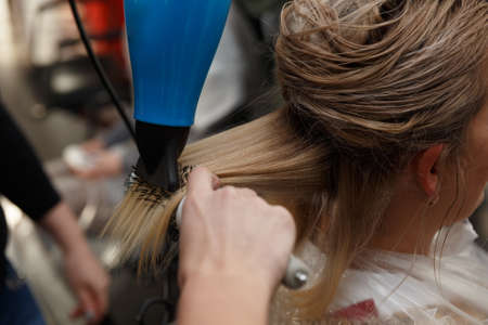 Hairdressers hands drying blond hair with blow dryer and round brush Stock fotó