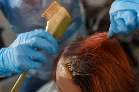 Hairdresser salon. Hair colouring in process. Woman dyeing hairs in red color.