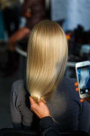 Hairdresser takes pictures on the smartphone result of hair coloring model. Rear view.