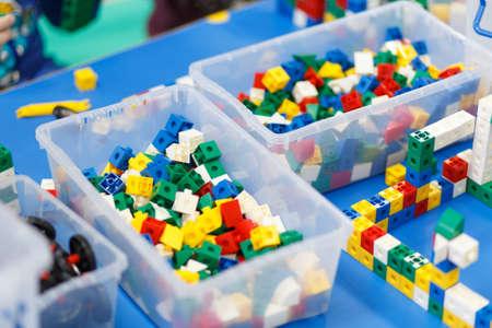 Close up van kinderhanden spelen met kleurrijke plastic stenen aan tafel. De eerste stappen voor de ontwikkeling van technisch denken. Stockfoto