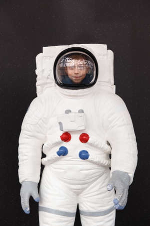 Portrait of a cute young boy in a space suit against the starry sky.