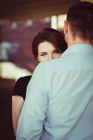 Portrait of young woman looking from behind the shoulder of her boyfriend. Love concept.