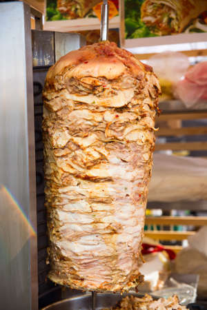 A large piece of chicken meat layered under fat cooking in a stainless steel grill machine often found in and outside of shawarma and kebab restaurants of the Middle East