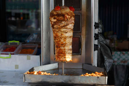 A large piece of chicken meat layered under fat cooking in a stainless steel grill machine often found in and outside of shawarma and kebab restaurants of the Middle East. 版權商用圖片