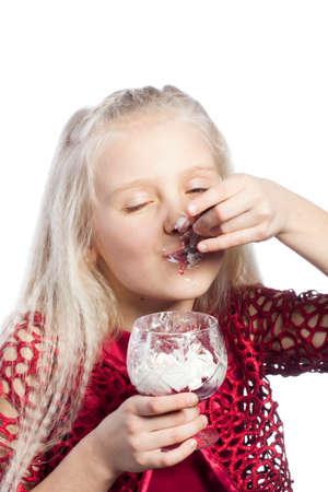 Beautiful blonde girl eating dessert on white background