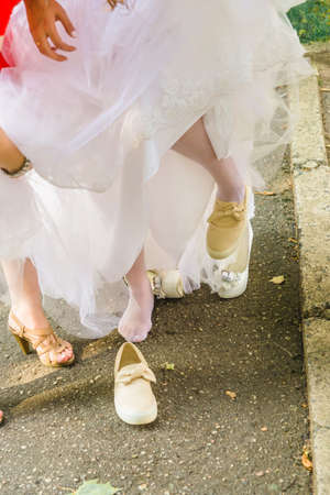 Bride change shoes sneakers on wedding walk in park Stock Photo
