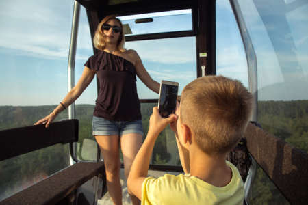 A boy takes pictures of his mother in the cab of the funicular