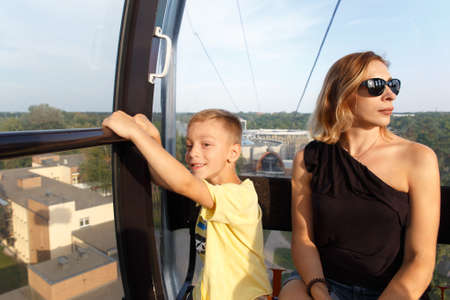 A boy with his mother in the cab of the funicular above a town