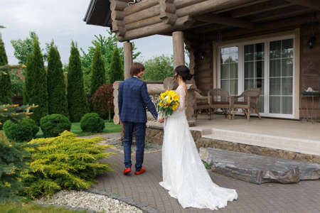 Newly married ready to enter in luxurious wooden mansion on wedding ceremony