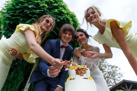 Newlyweds and bridesmaids have fun and eat wedding cake together in the fresh air on wedding banquet.