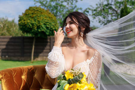 The charming bride keeps a wedding bouquet and sitting on the yard