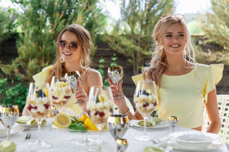 Beautifyul young bridesmaids drink champagne at an outdoor table Standard-Bild