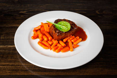 Beef steak with mini carrots and Demiglace sauce in white plate on wooden table