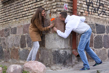 Young happy amorous cheerful couple with gerbera playing on the street of old city