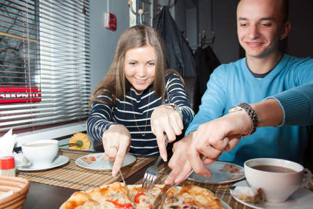Couple in love eating pizza and having fun in a cafe