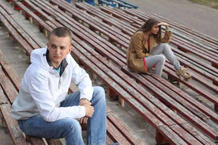 Sad boy and a girl sitting on tribunes of empty stadium.The concept resentment of misunderstanding. Quarrel in a relationship in street.
