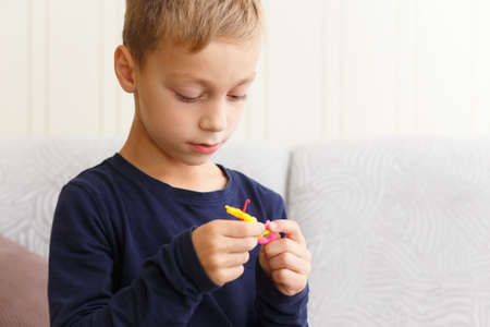 Boy weaves bracelet of rubber rings at home on the couch