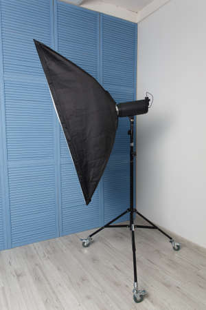 Studio flash with soft box standing in the corner of the Studio. Side view.